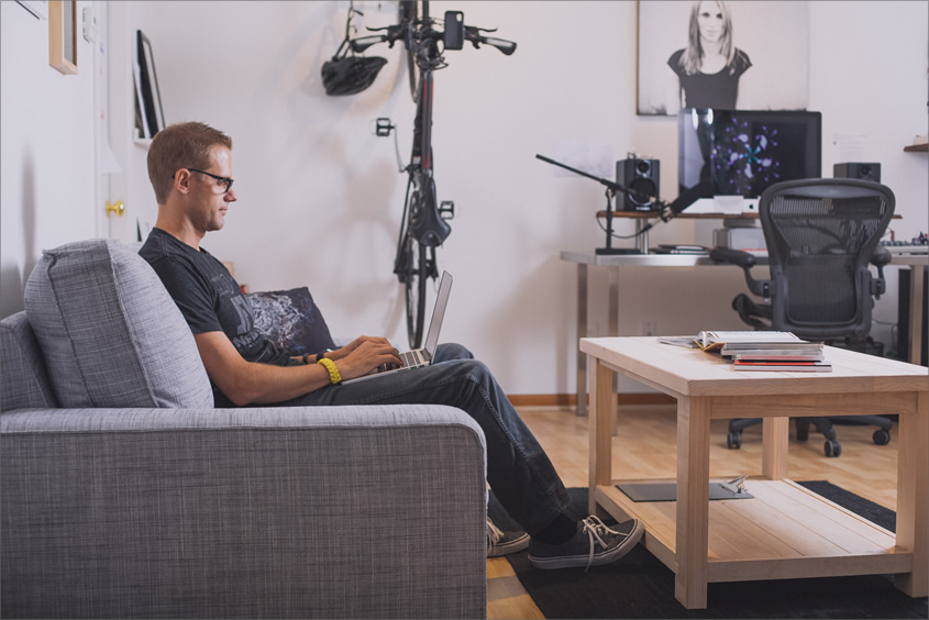 A photo of Cameron Moll sitting on the sofa in his office, using a laptop, with an iMac and speakers on the far right.