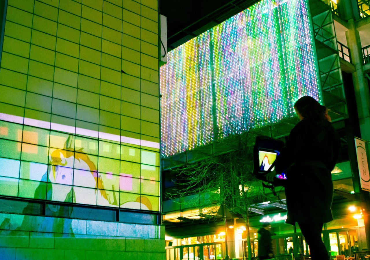 A photo of the projector being used outside on a wall.