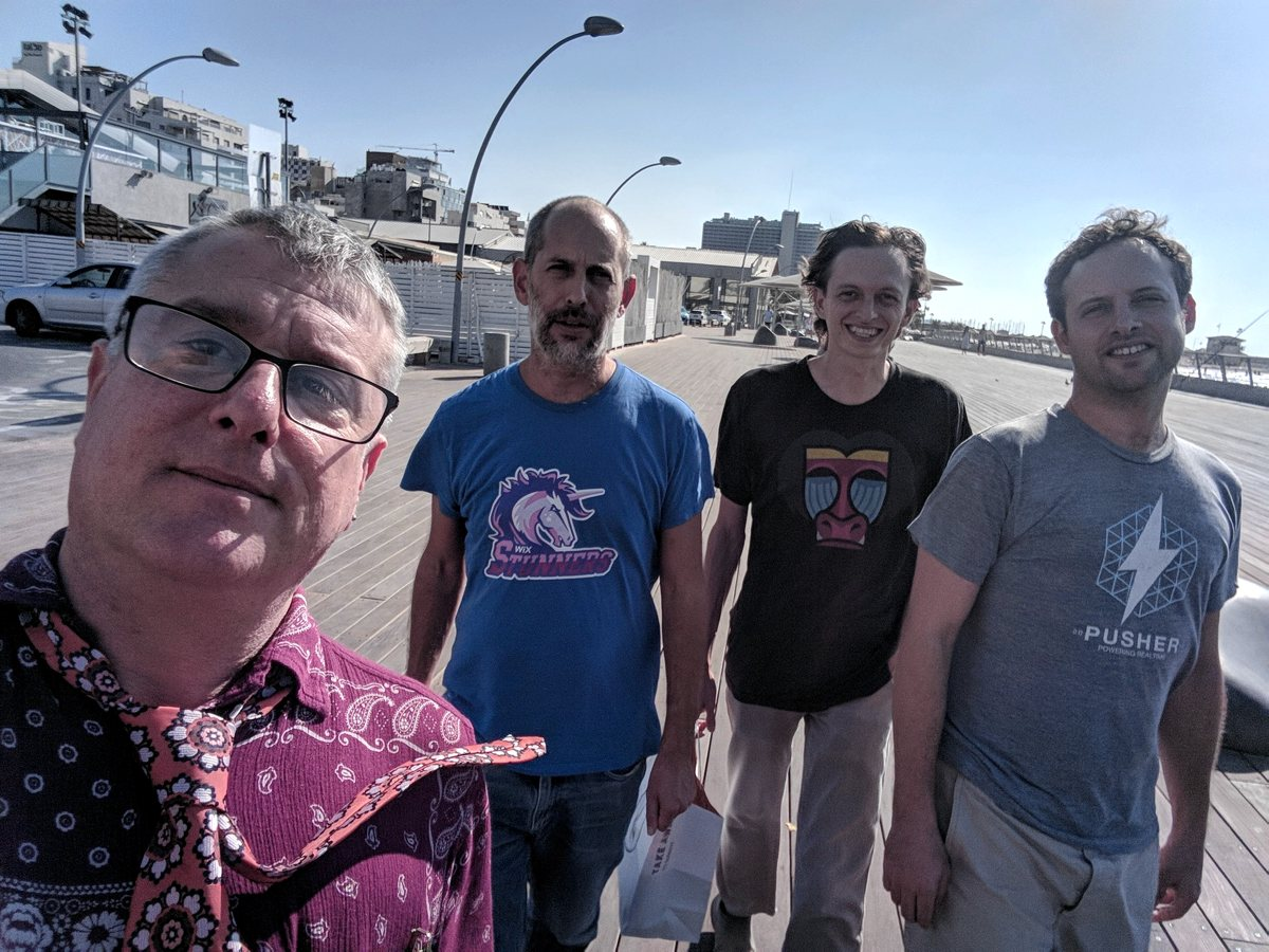 Photo of Bruce, Arnon, Tom, and Ido on a boardwalk. The latter three are wearing shirts advertising web deb companies and services.